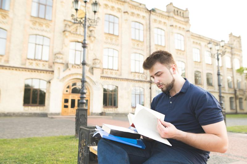 Man wearing a beard sitting on a bench on the background of a university building and reading a book. Serious student sitting on a bench at a university campus royalty free stock image