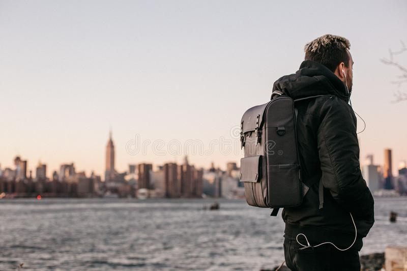 Man Wearing Black Bubble Jacket And Black Leather Backpack Near Bay Free Public Domain Cc0 Image