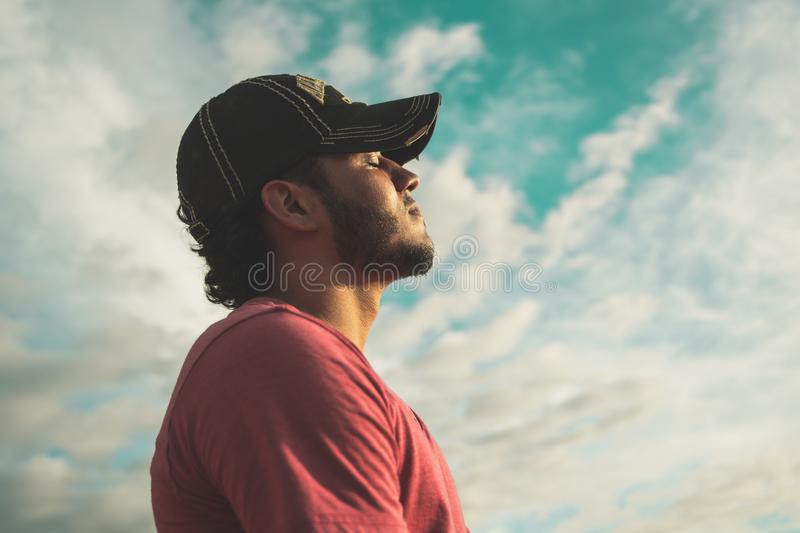 Man Wearing Black Cap With Eyes Closed Under Cloudy Sky royalty free stock photos