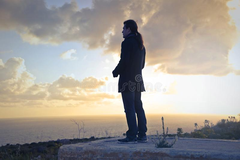 Man Wearing Black Coat Standing Near Sea during Golden Hour stock image
