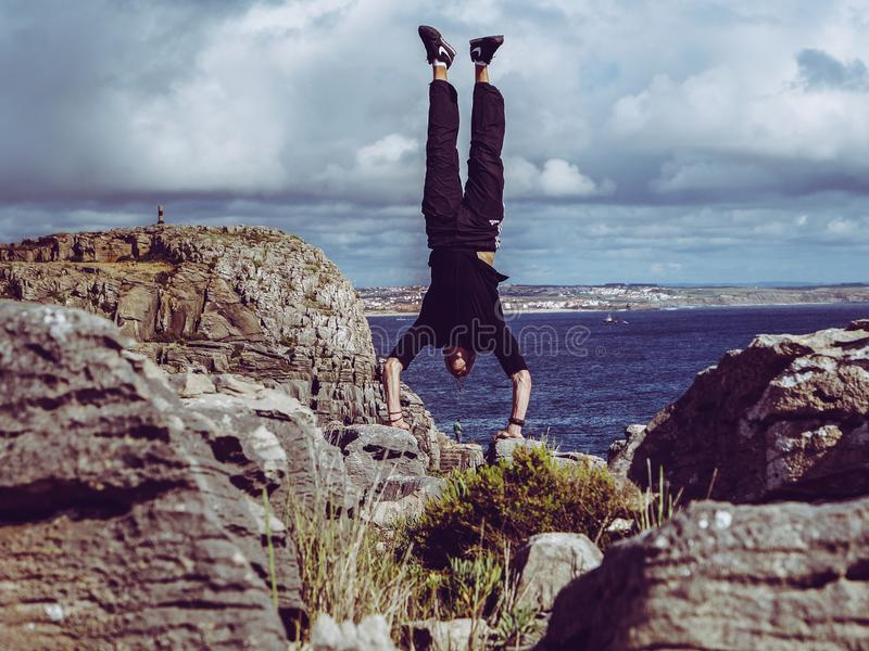 Man Wearing Black Dress Shirt and Burgundy Pants Hand Standing on Rock Formations Across Sea royalty free stock image