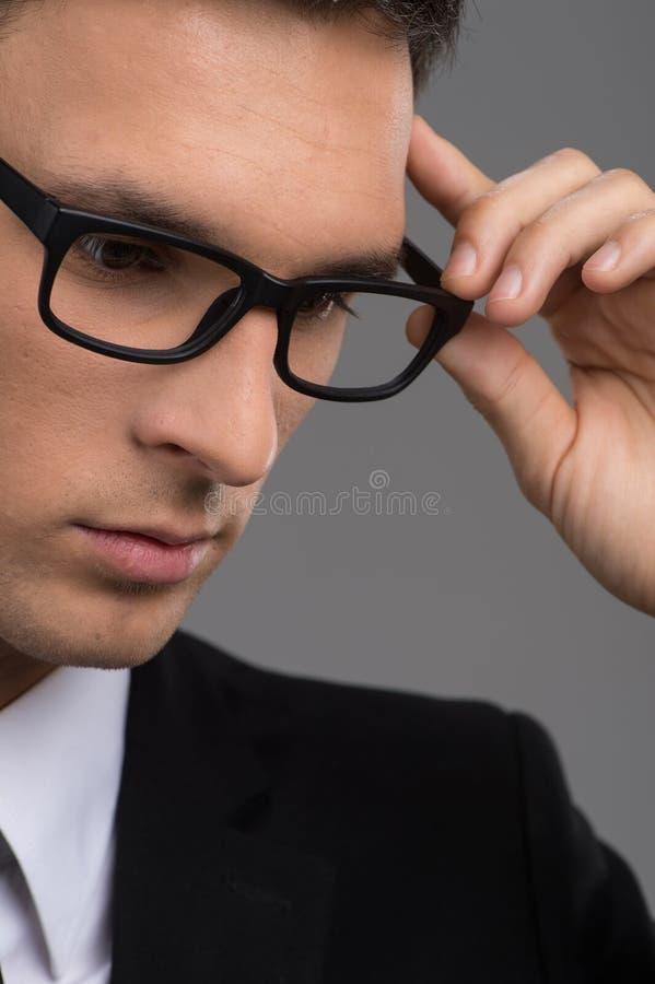Man wearing black glasses on grey background. stock image