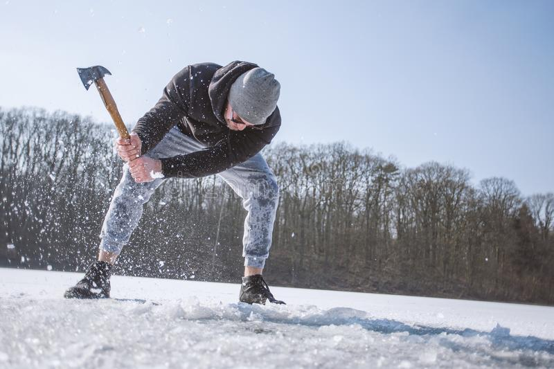 Man Wearing Black Hooded Jacket, Gray Knit Cap, Gray Pants, and Black Shoes Holding Brown Handled Axe While Bending on Snow stock images