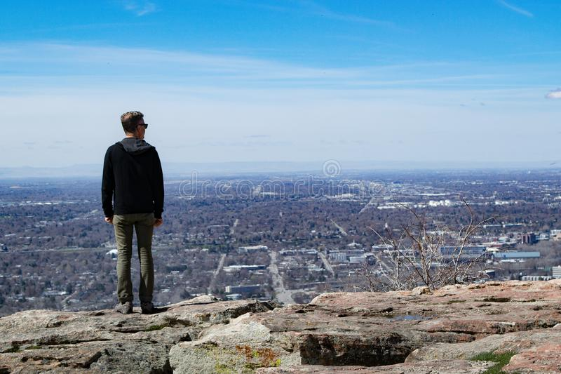 Man Wearing Black Jacket Standing on Rock Monolith royalty free stock photography
