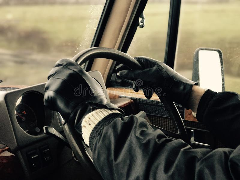 Man wearing black leather driving gloves in vintage vehicle stock photos