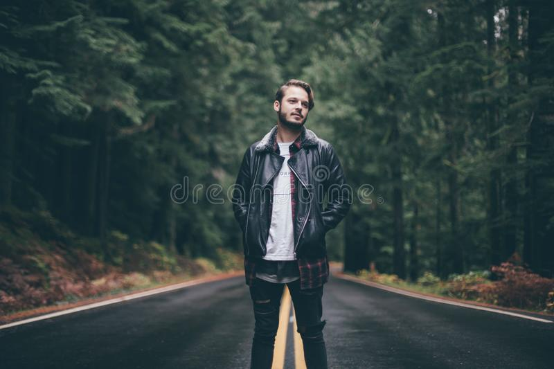 Man Wearing Black Leather Jacket Standing On Highway In The Middle Of Green Trees Free Public Domain Cc0 Image