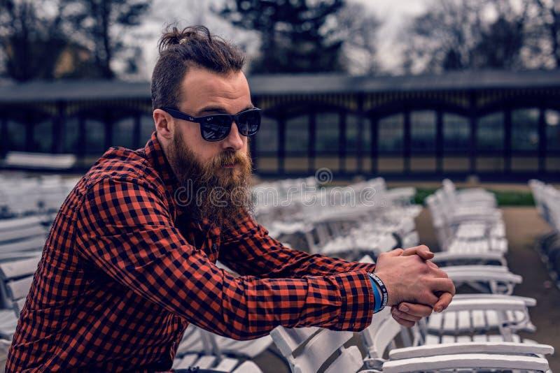 Man Wearing Black And Red Checkered Long Sleeve Shirt Wearing Black Wayfarer Sunglasses Sitting On White Wooden Chair Free Public Domain Cc0 Image