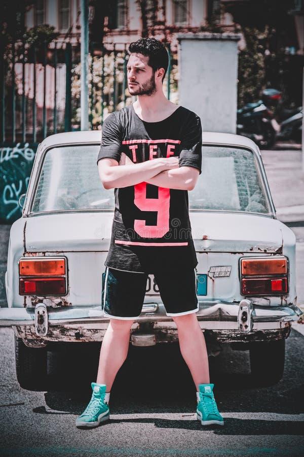 Man Wearing Black Scoop-neck T-shirt and Black Gym Shorts Standing Behind White Vehicle royalty free stock image