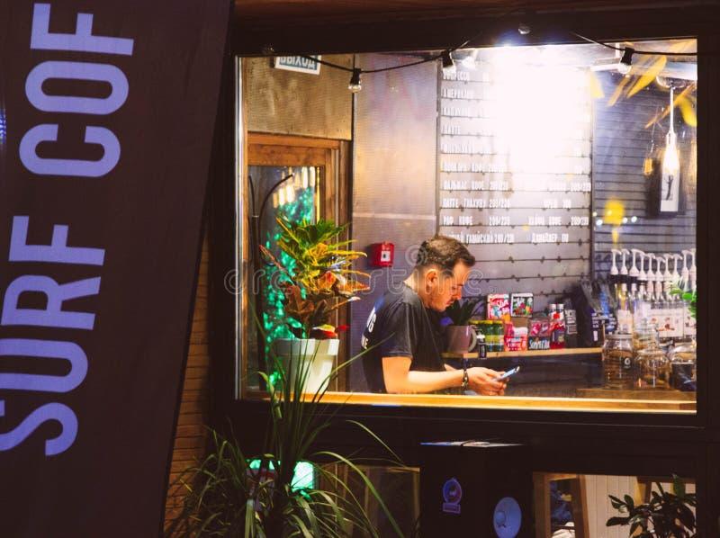 Man Wearing Black Shirt Holding Smartphone Sitting Near Window stock images