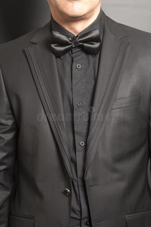 Man wearing a black suit and bow tie on gray. Background royalty free stock image