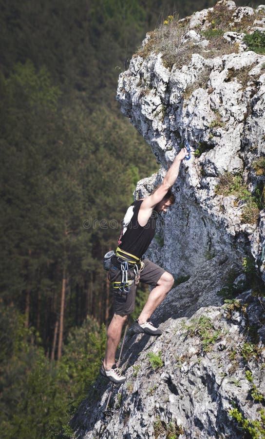 Man Wearing Black Tank Top and Brown Shorts Climbing Rock royalty free stock image
