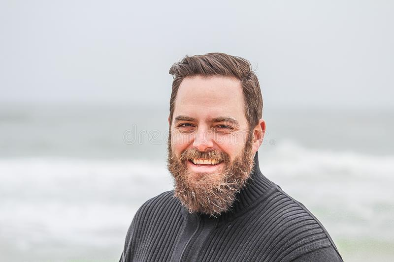 Man Wearing Black Zip-up Jacket Near Beach Smiling at the Photo stock photography