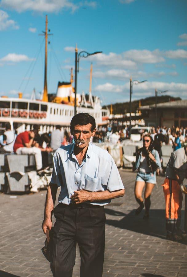 Man Wearing Blue Button-up T-shirt and Black Dress Pants Smoking Cigarette stock image