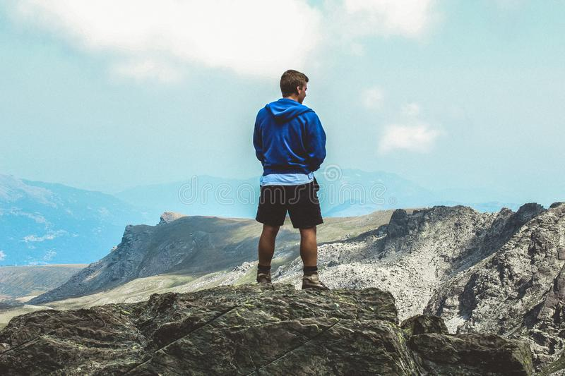Man Wearing Blue Hoodie Standing on Top of Mountain stock images