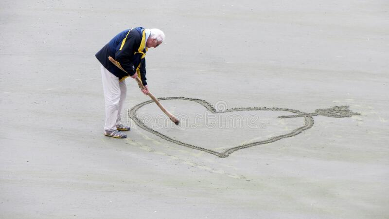 Man Wearing Blue Jacket Holding A Brown Stick Towards The Heart Drawn On Sand Free Public Domain Cc0 Image
