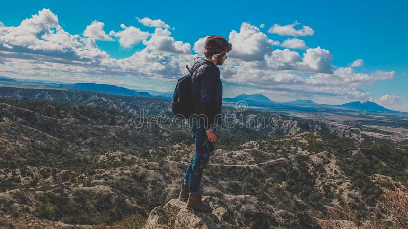 Man Wearing Blue Jeans Standing on Gray Stone Fragment Under Cloudy Sky royalty free stock image