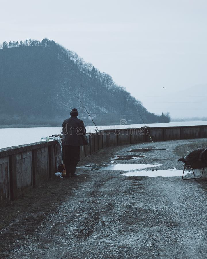Man Wearing Brown Coat Near a Body of Water With Fishing Rods at Daytime stock photos