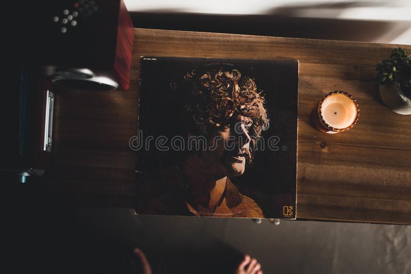 Man Wearing Brown Collared Shirt Photo on Brown Wooden Cabinet royalty free stock photos