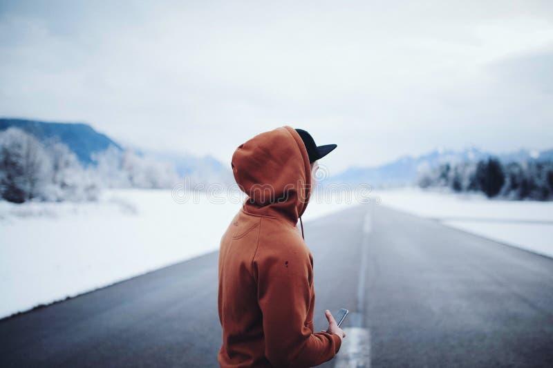 Man Wearing Brown Hoodie in Road stock image