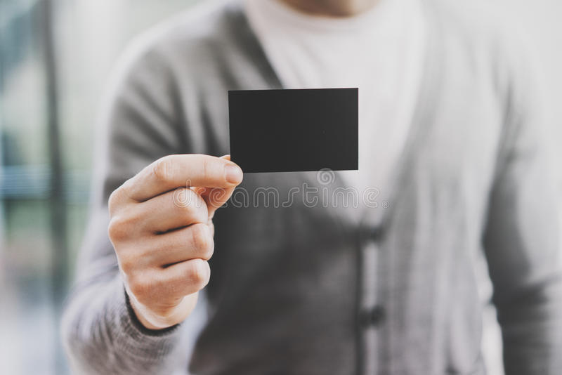 Man wearing casual shirt and showing blank black business card. Blurred background. Horizontal mockup stock photo