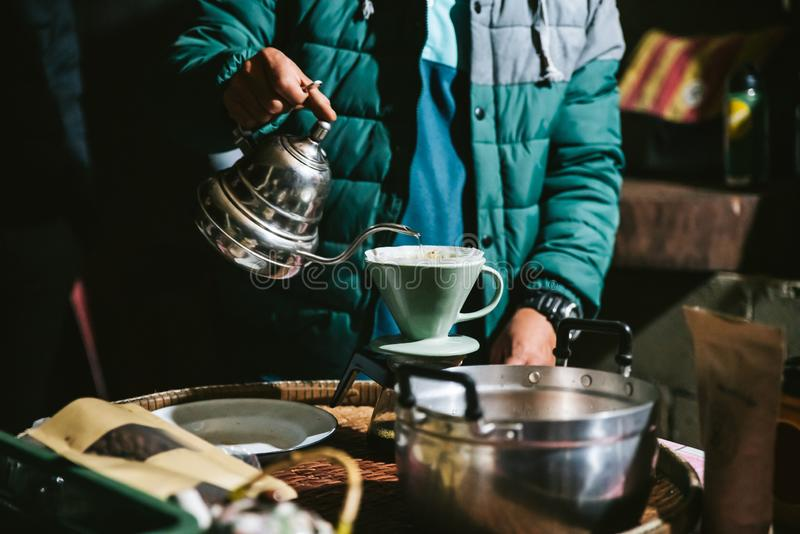 Man wearing coat and making pour-over coffee with alternative method called Dripping. Coffee grinder. stock photos