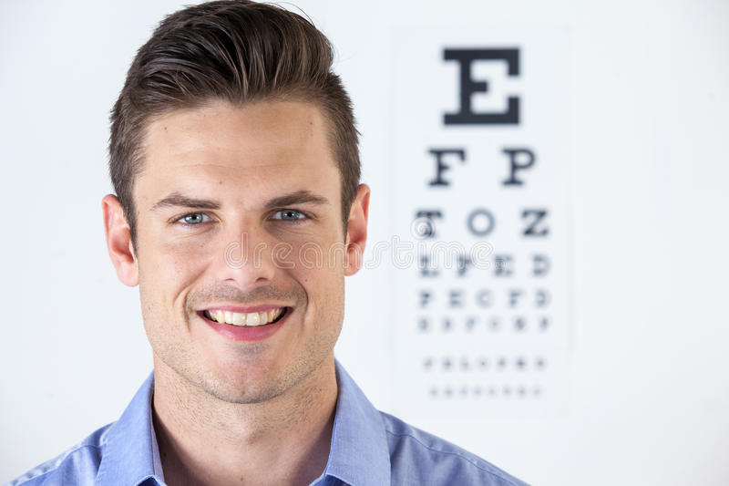 Man wearing contact lens with eye chart in background. Portrait of man wearing contact lens with eye chart in background stock images
