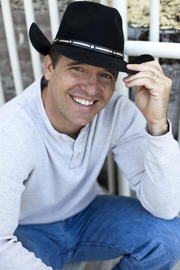 Man wearing cowboy hat. A friendly, smiling man wearing a cowboy hat holding brim royalty free stock photography