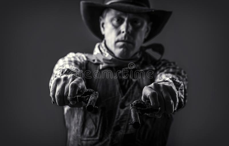 Man wearing cowboy hat, gun. Portrait of a cowboy. West, guns. Portrait of a cowboy. American bandit in mask, western. Man with hat. Portrait of farmer or royalty free stock photo