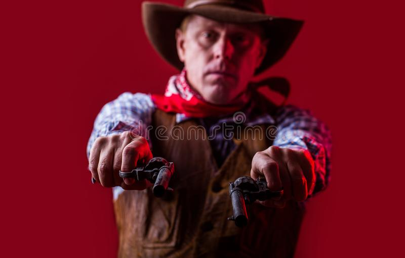 Man wearing cowboy hat, gun. Portrait of a cowboy. West, guns. Portrait of a cowboy. American bandit in mask, western royalty free stock photo