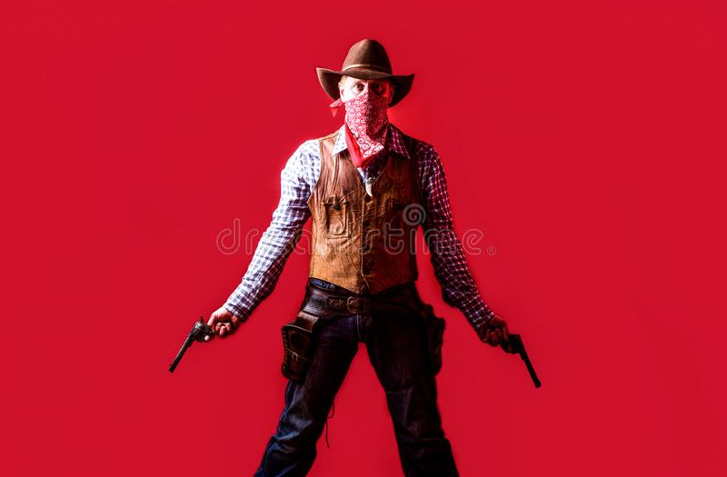 Man wearing cowboy hat, gun. West, guns. Portrait of a cowboy. owboy with weapon on red background. American bandit in. Mask, western man with hat. Portrait of royalty free stock image
