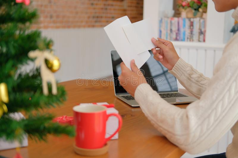 Man opening sending christmas letter greeting card holiday wishes with xmas decoration. Man wearing cream sweater opening sending christmas letter greeting card stock photos
