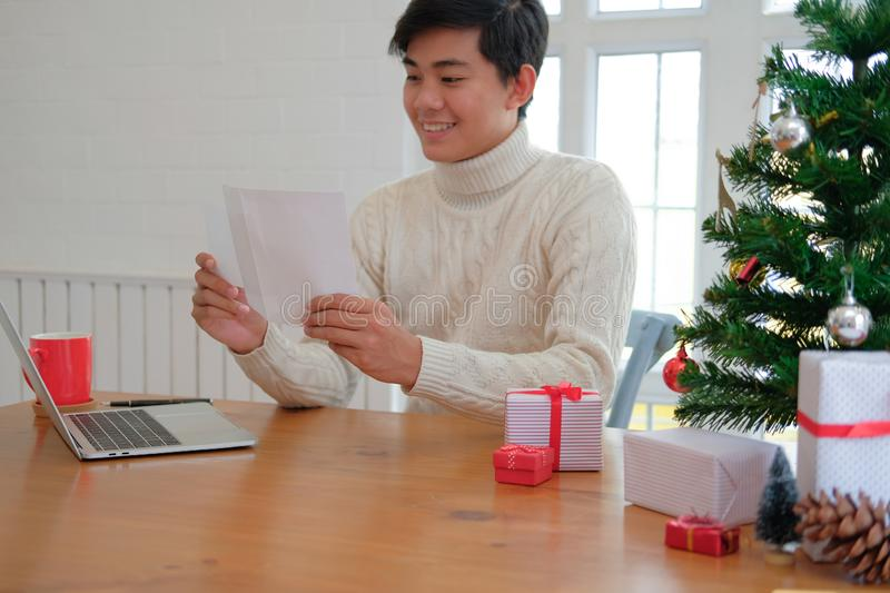 Man opening sending christmas letter greeting card holiday wishes with xmas decoration. Man wearing cream sweater opening sending christmas letter greeting card royalty free stock photo