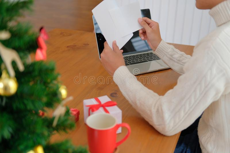Man opening sending christmas letter greeting card holiday wishes with xmas decoration. Man wearing cream sweater opening sending christmas letter greeting card stock photography