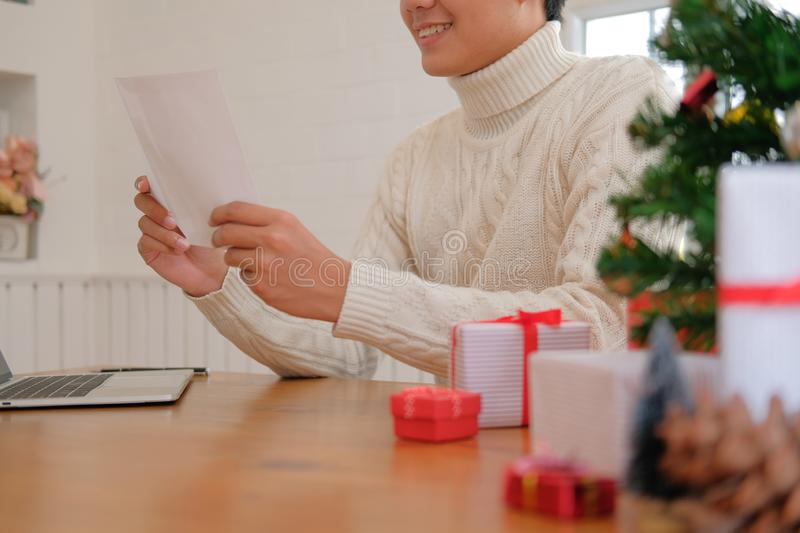 Man opening sending christmas letter greeting card holiday wishes with xmas decoration. Man wearing cream sweater opening sending christmas letter greeting card royalty free stock image
