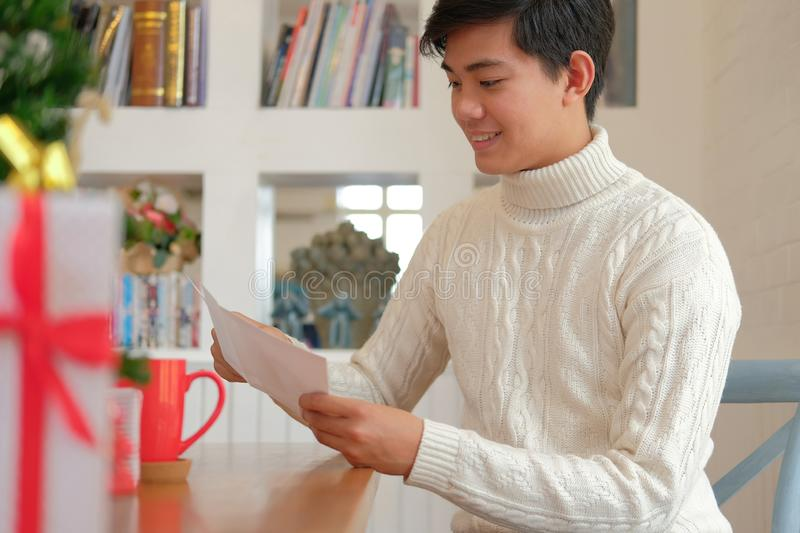 Man opening sending christmas letter greeting card holiday wishes with xmas decoration. Man wearing cream sweater opening sending christmas letter greeting card royalty free stock photography