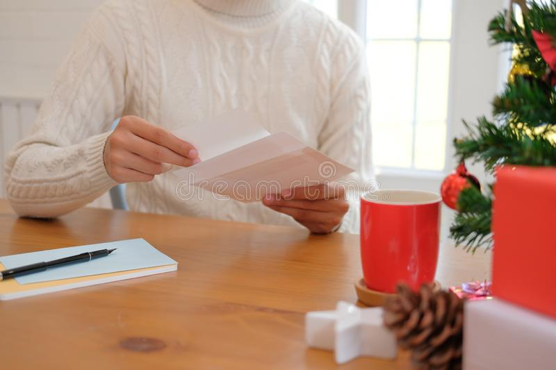 Man opening sending christmas letter greeting card holiday wishes with xmas decoration. Man wearing cream sweater opening sending christmas letter greeting card stock photo