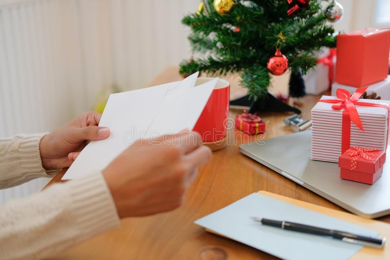 Man opening sending christmas letter greeting card holiday wishes with xmas decoration. Man wearing cream sweater opening sending christmas letter greeting card royalty free stock photos