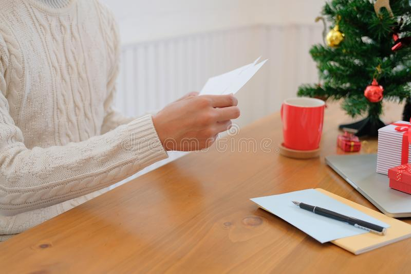 Man opening sending christmas letter greeting card holiday wishes with xmas decoration. Man wearing cream sweater opening sending christmas letter greeting card royalty free stock images