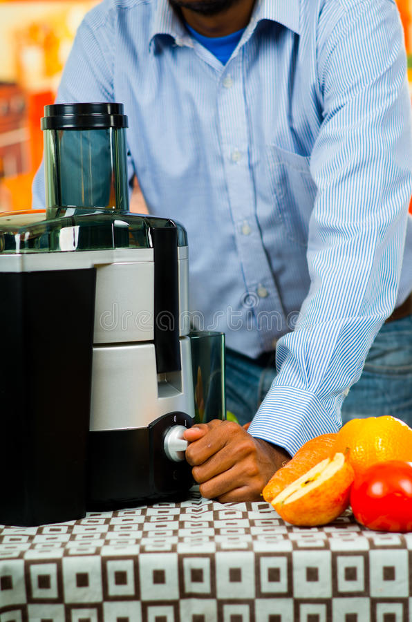 Man wearing denim jeans and shirt using juice maker, leaning onto table with machine, healthy lifestyle concept stock images