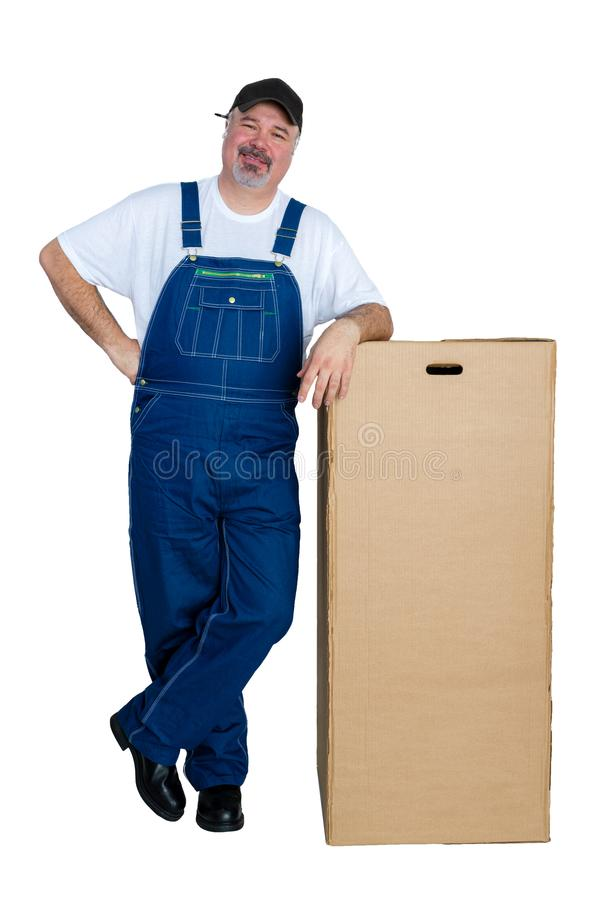Man wearing dungarees leaning against large box stock photography