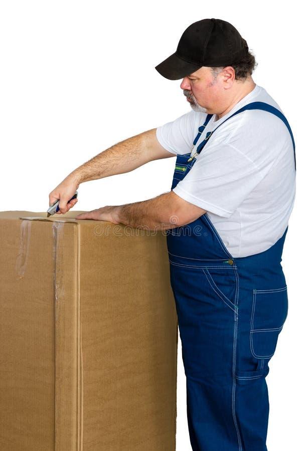 Man wearing dungarees opening large cardboard box royalty free stock photo