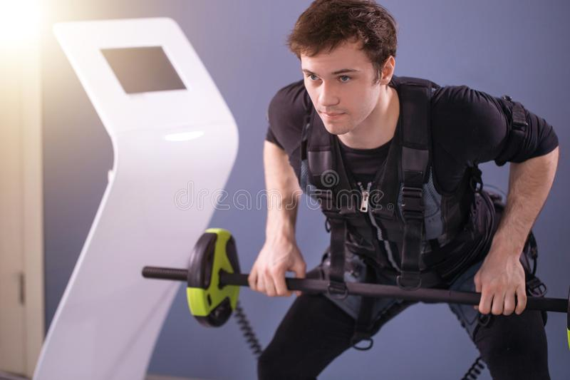 Man working out EMS training with barbell closeup, power pose royalty free stock images