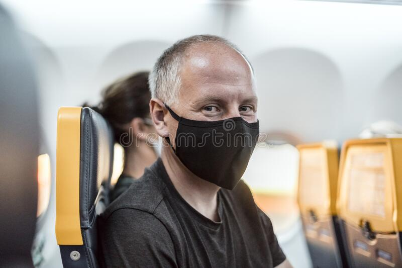 Man wearing face mask sitting in the airplane royalty free stock photos