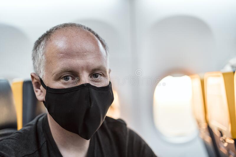 Man wearing face mask sitting in the airplane stock photography