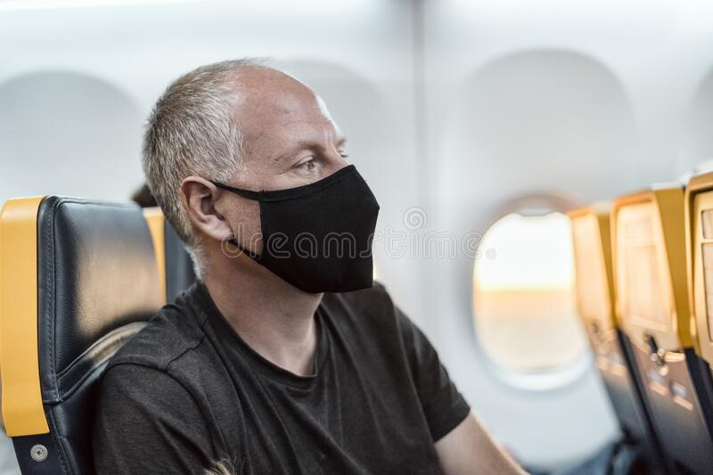 Man wearing face mask sitting in the airplane stock images