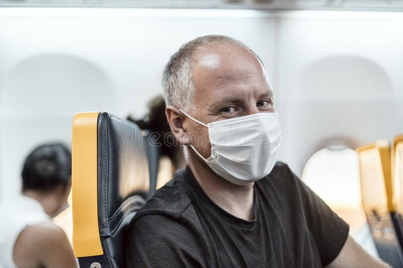 Man wearing face mask sitting in the airplane royalty free stock image