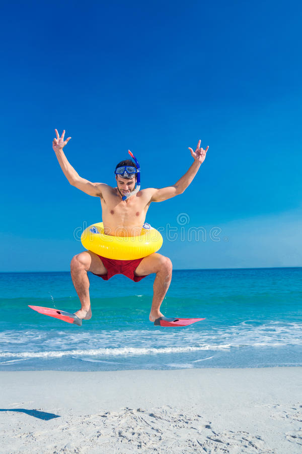 Man wearing flippers and rubber ring at the beach. On a sunny day royalty free stock image