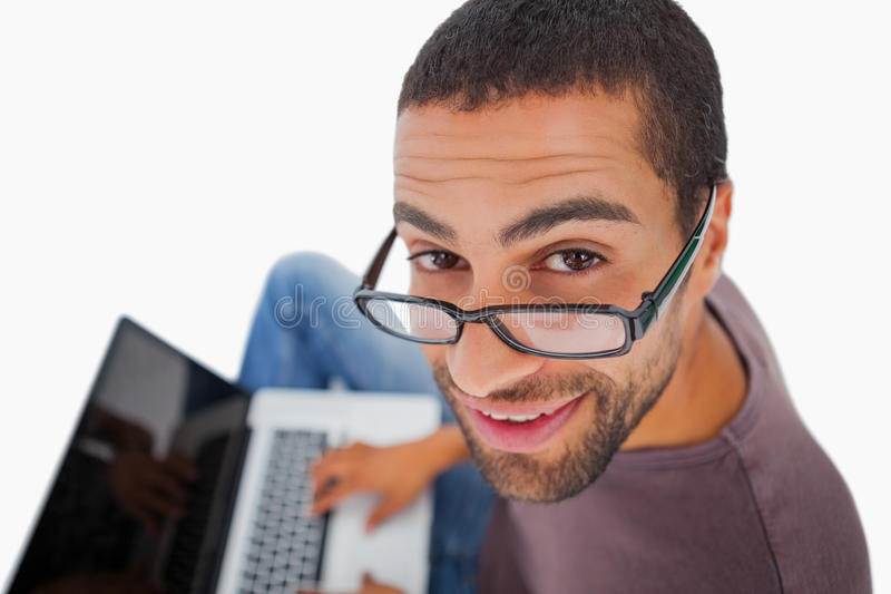 Man wearing glasses sitting on floor using laptop and smiling up