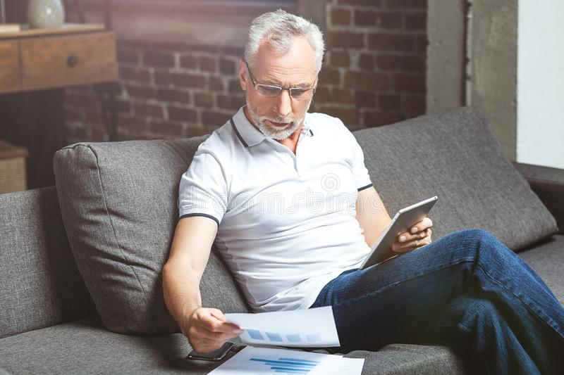 Man wearing glasses using on digital tablet royalty free stock image