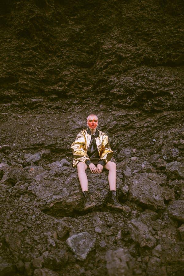 Man Wearing Gold Jacket Sitting on Stone stock photo